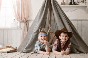 Two little boys in the image of cowboys and Indians play in his room